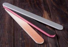 Dossier de clou trois avec un abrasif différent d'isolement sur le fond en bois foncé Photo libre de droits