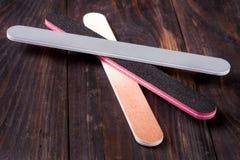 Dossier de clou trois avec un abrasif différent sur le fond en bois foncé Photographie stock