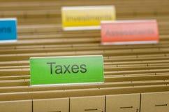 Dossieromslag met Belastingen wordt geëtiketteerd die Stock Afbeeldingen
