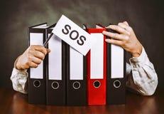 Dossieromslagen met handen en S.O.S.teken Royalty-vrije Stock Foto's