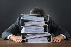 Dossiers frustrants de With Lot Of d'homme d'affaires sur le bureau Images stock