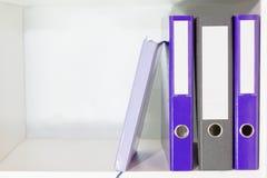Dossiers pour des documents et planificateur sur des étagères à livres Images stock