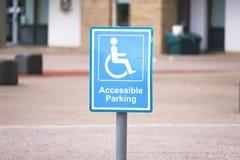 Dost?pny parking znak przy szko?? dla niepe?nosprawnych kierowc?w fotografia royalty free