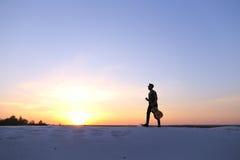 Dostojny Arabski facet chodzi z gitarą w rękach na piaskowatym wzgórzu w des Fotografia Stock