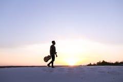 Dostojny Arabski facet chodzi z gitarą w rękach na piaskowatym wzgórzu w des Obraz Stock