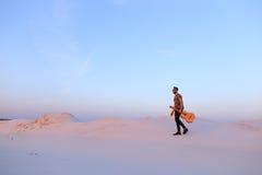 Dostojny Muzułmański młody człowiek chodzi z gitarą w rękach przez dese fotografia stock