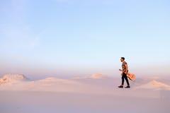 Dostojny Muzułmański młody człowiek chodzi z gitarą w rękach przez dese Zdjęcie Stock