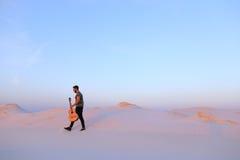 Dostojny Muzułmański młody człowiek chodzi z gitarą w rękach przez dese obrazy royalty free