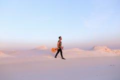 Dostojny Muzułmański młody człowiek chodzi z gitarą w rękach przez dese fotografia royalty free