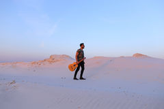 Dostojny Muzułmański młody człowiek chodzi z gitarą w rękach przez dese obraz royalty free