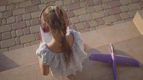 Dosyć śliczna mała dziewczynka czyta książkę w hełmofonach mały płaski lying on the beach na ganeczku Dziecko wydaje czas zdjęcie wideo