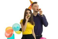 Dosyć śmieszna dziewczyna i zakończenie faceta mienia balonów i ciosów rogów Zdjęcia Royalty Free