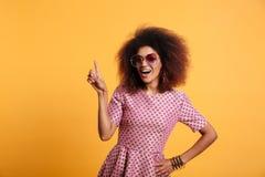 Dosyć afro amerykańska retro kobieta wskazuje wi z afro fryzurą Zdjęcie Stock