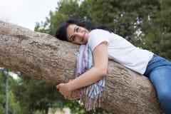 Dosyć atrakcyjna kobieta jest ubranym kauzalny odzieżowego i ściska drzewa w zielonym parku fotografia royalty free
