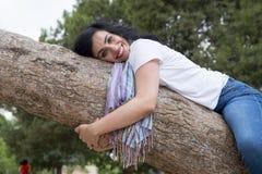Dosyć atrakcyjna kobieta jest ubranym kauzalny odzieżowego i ściska drzewa w zielonym parku obrazy royalty free