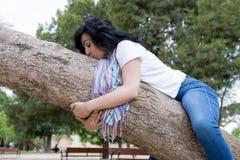 Dosyć atrakcyjna kobieta jest ubranym kauzalny odzieżowego i ściska drzewa w zielonym parku zdjęcie royalty free