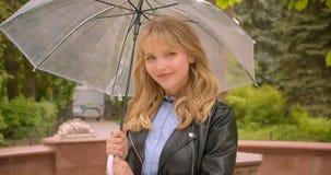 Dosyć caucasian blondynka uczeń otwiera parasolowego narządzanie dla deszczu jest radosny w zielonym miasto parku zbiory