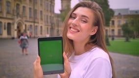 Dosyć caucasian dziewczyna pokazuje zieleń ekran i ono uśmiecha się szczęśliwie i relaksuje na miastowym widoku, dzień