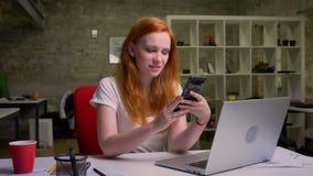 Dosyć caucasian imbirowa kobieta siedzi przy miejsce pracy i trzyma jej telefon patrzeje ekran ono, zrelaksowany, za
