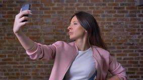 Dosyć caucasian kobieta bierze obrazki ona, patrzeje sieci kamerę na jej telefonie skupiającym się, podczas gdy być w czerwieni zbiory