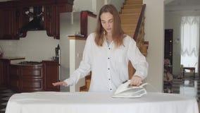 Dosyć caucasian młoda kobieta taniec podczas gdy robić sprzątaniu w domu Zabawy śliczna gospodyni domowa odprasowywa ona odzieżow zbiory