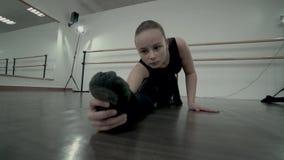 Dosyć demure i smutna Nastoletnia balerina ubierająca w czarnych leotards rozciąga nogi uważnie zbiory