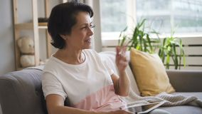 Dosyć dojrzała dama siedzi na leżance w nowożytnym mieszkaniu jest opowiadająca, gestykulujący, zbiory wideo