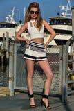 Dosyć elegancka młoda kobieta w żeglarzów skrótach, wierzchołku i okularach przeciwsłonecznych pozuje dosyć na molu, Obrazy Stock