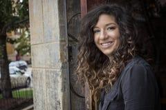 Dosyć Kędzierzawa Z włosami kobieta w Restauracyjnym drzwi Fotografia Royalty Free