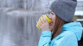 Dosyć Kaukaska dziewczyna marzy patrzeć w dystansowy trwanie plenerowego z filiżanką herbaciany pobliski nadbrzeżny obraz stock