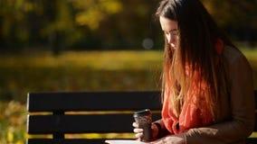 Dosyć Kaukaska kobieta Pije kawę i czytanie na ławce w jesień parku, Plenerowy relaksu pojęcie zbiory wideo