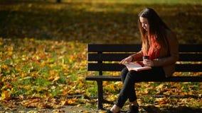 Dosyć Kaukaska kobieta Pije kawę i czytanie na ławce w jesień parku, Plenerowy relaksu pojęcie zdjęcie wideo