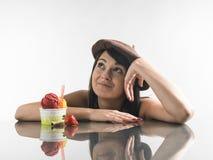 Dosyć, młoda kobieta patrzeje kawowych kubki na jaskrawym tle Zdjęcia Royalty Free
