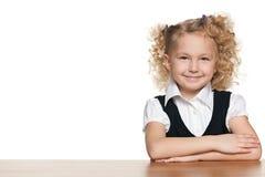 Dosyć mała uczennica przy biurkiem Zdjęcia Royalty Free