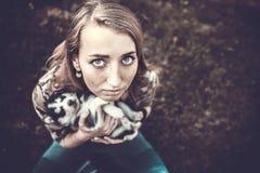 Dosyć mały łuskowaty szczeniak plenerowy w kobiet rękach obrazy stock