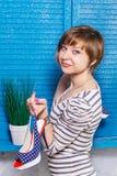 Dosyć nastoletnia dziewczyna trzyma nową wysokość heeled kropkowanych buty na jej palcu Błękitny jalousie okno z zielonych roślii obrazy stock