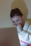 Dosyć nastoletnia jest ubranym opatrunkowa toga ogląda jej laptop w dar Zdjęcia Royalty Free
