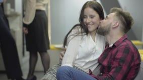 Dosyć nieśmiała dama siedzi blisko atrakcyjnego brodatego mężczyzny w przypadkowym przymknięciu w nowożytnym biurze Facet całuje  zdjęcie wideo