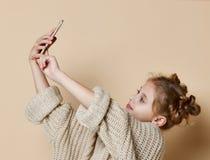 Dosyć nowożytna dziewczyna uśmiecha się selfie i robi na smartphone w ogromnym pulowerze obraz stock