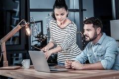 Dosyć odpowiedzialna kobiety pozycja i wskazywać przy laptopem fotografia royalty free