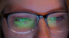 Dosyć piękni oczy w górę caucasian hacker dziewczyny są przyglądającym ekranem z informacją i ono odbija jak obrazki