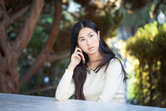 Dosyć poważna azjatykcia kobieta opowiada na telefonie Obraz Royalty Free