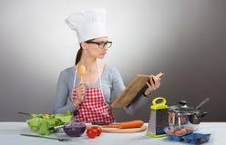 Dosyć poważny kobiety kucharstwo z starą książką kucharska zdjęcia stock