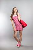 Dosyć radosna mała dziewczynka w pasiastej sukni pozuje w studiu Fotografia Royalty Free