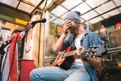 Dosyć radosnego męskiego gitarzysty wykończeniowy występ w barze fotografia royalty free