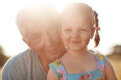 Dosyć radosny żeński dziecko z dwa piggytails, stojaki cloely jej dziad, zabawę wpólnie, wydaje czas wolnego na łąkowym dur fotografia stock