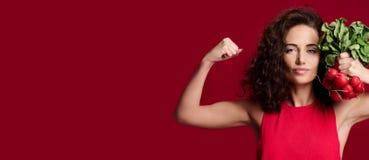 Dosyć rozochoconego potomstwo sporta kobiety chwyta świeża rzodkiew z zielenią opuszcza i wskazujący palec dietetyczka zdjęcia royalty free