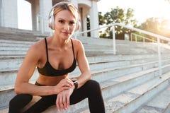 Dosyć silnej potomstwo sportów kobiety słuchająca muzyka i używać zegarek Zdjęcie Stock