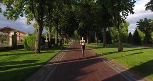 Dosyć sportowa kobieta jogging w pogodnym parku Frontowy widok zbiory