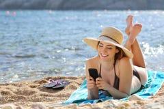 Dosyć szczęśliwa kobieta czyta mądrze telefon na plaży Fotografia Royalty Free